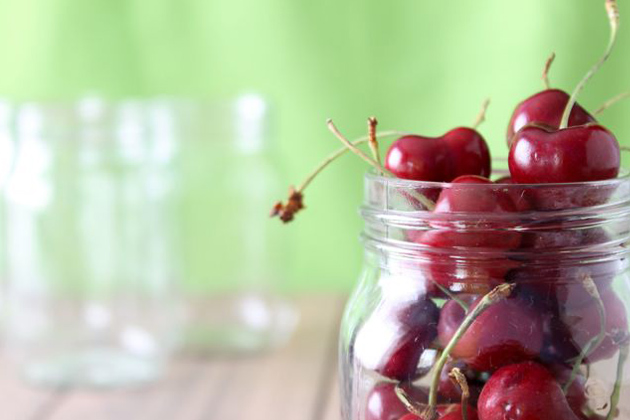 Cherries in glass jar against green backdrop