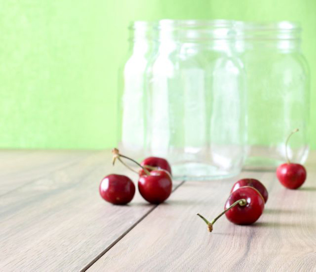 A couple of cherries in front of glass jar